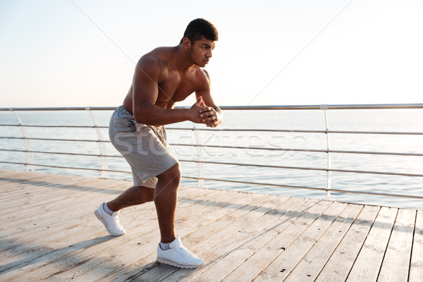 Young shirtless afro american sportsman doing squats on the pier Stock photo © deandrobot