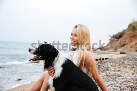Happy woman relaxing with her dog on the beach Stock photo © deandrobot