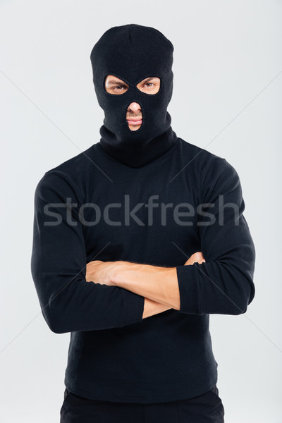 Portrait of man in balaclava standing with arms crossed Stock photo © deandrobot