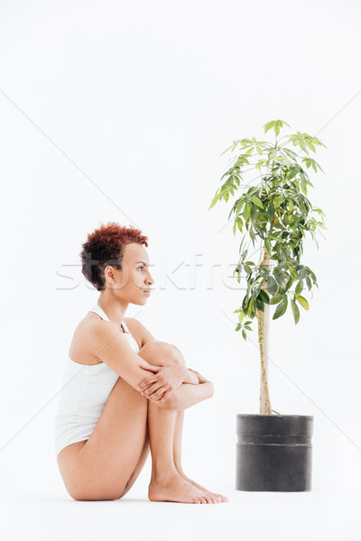 Pensive woman sitting and thinking near small tree in pot Stock photo © deandrobot