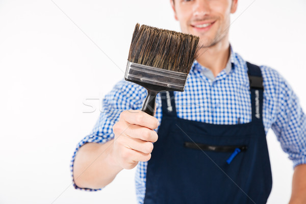 Cropped image of smiling male builder holding paint brush Stock photo © deandrobot