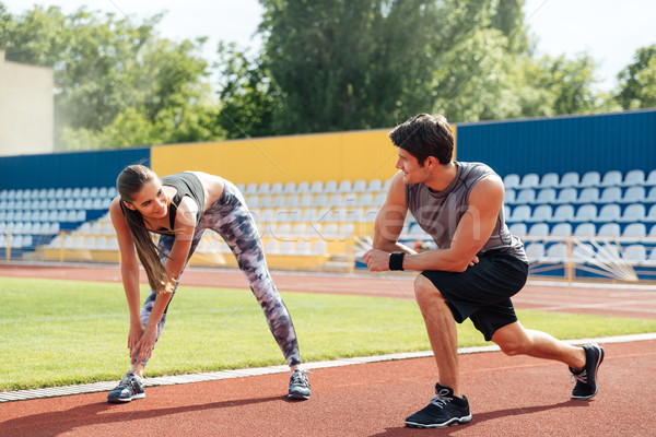 Couple talking and warming up before running on stadium Stock photo © deandrobot