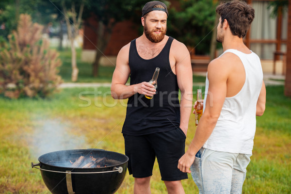 Two men holding a beer bottle while preparing barbecue Stock photo © deandrobot