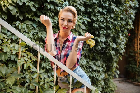 Pinup girl holding bunch of fresh grape outdoors Stock photo © deandrobot
