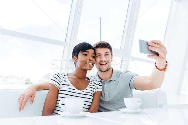 Smiling young couple making selfie photo on smartphone indoors Stock photo © deandrobot