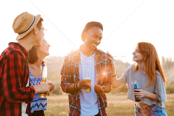 Group of smiling young friends drinking beer and soda outdoors Stock photo © deandrobot