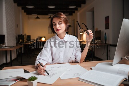 Woman fashion designer drawing sketches at the table in office Stock photo © deandrobot