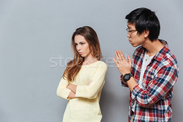 Young asian man asking for forgiveness his girlfriend Stock photo © deandrobot