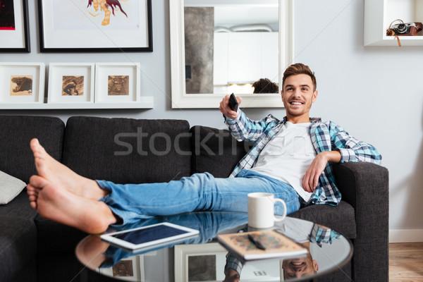 Homme télécommande regarder tv Photo stock © deandrobot