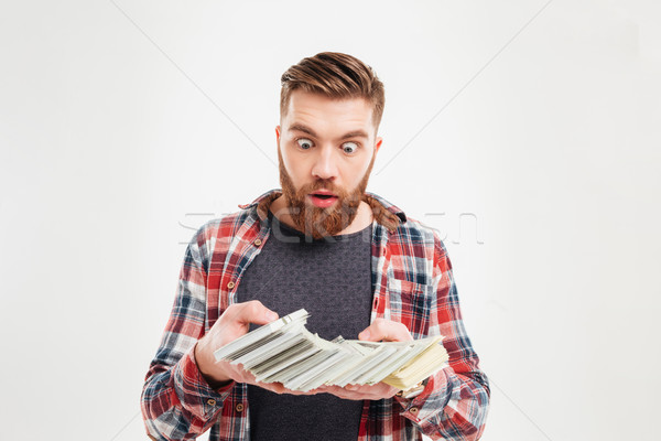 Excited bearded man in plaid shirt looking at money banknotes Stock photo © deandrobot