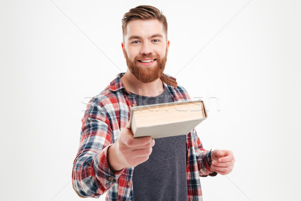 Stock photo: Smiling bearded guy in plaid shirt giving book to camera