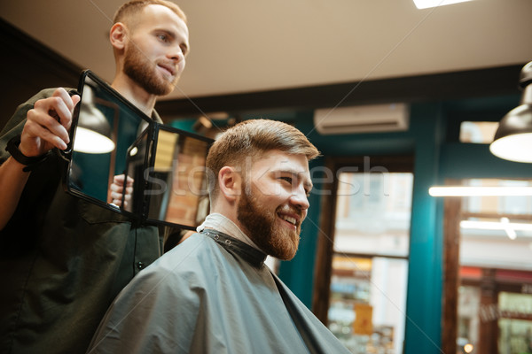 Handsome man getting haircut by hairdresser in barbershop Stock photo © deandrobot
