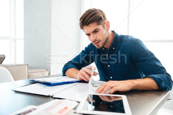 Elfoglalt fiatalember ül otthon gondolkodik pénzügyek Stock fotó © deandrobot