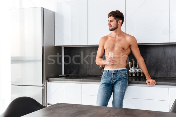Shirtless man standing and drinking water on the kitchen Stock photo © deandrobot