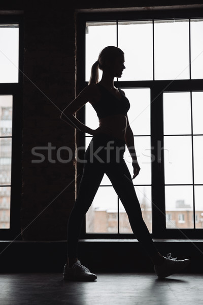 Silhouette of woman athlete standing near the window Stock photo © deandrobot