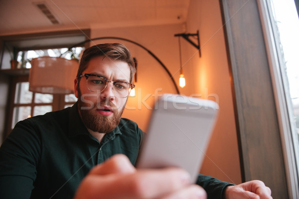 Amazed schoked man reading message or recieving photo image Stock photo © deandrobot