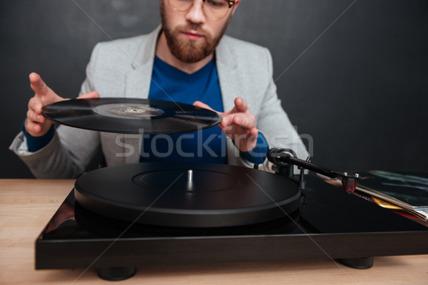 Concentrated young man in glasses using turntable and vinyl record Stock photo © deandrobot