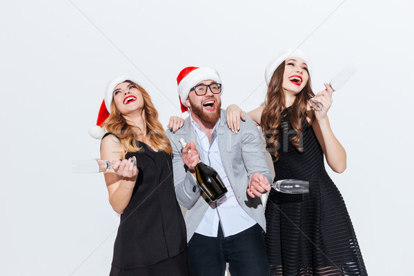 Three people in santa claus hats drinking champagne and laughing Stock photo © deandrobot