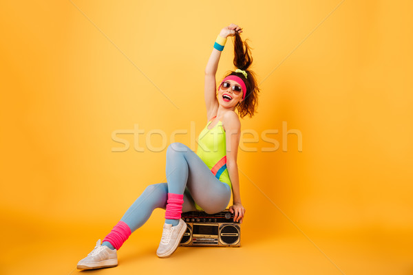 Cheerful woman athlete sitting on retro boombox and having fun Stock photo © deandrobot