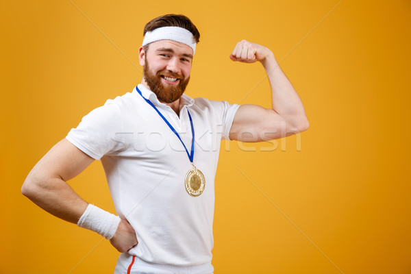 Happy young sportsman with medal showing his biceps. Stock photo © deandrobot