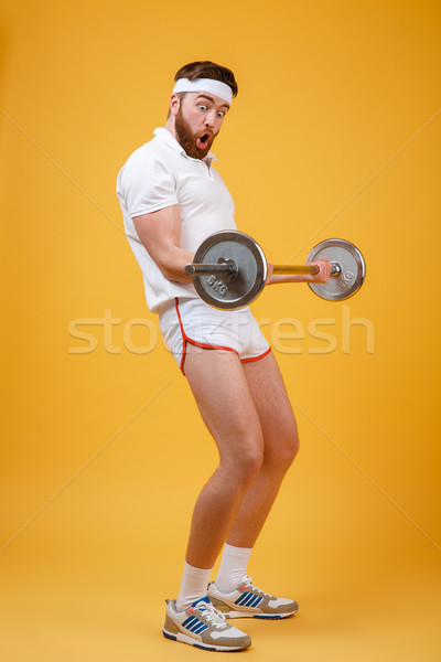 Portrait of a young bearded fitnes man doing workout Stock photo © deandrobot
