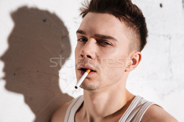 Handsome man with cigarette posing isolated over wall background Stock photo © deandrobot