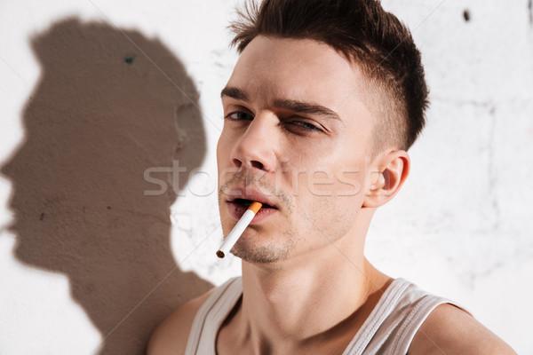 красивый мужчина сигарету позируют изолированный стены портрет Сток-фото © deandrobot