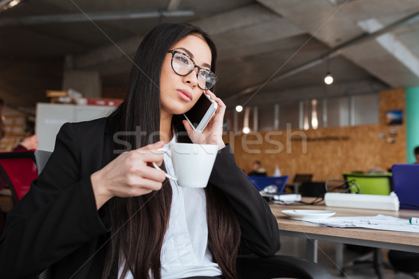 Stock photo: Businesswoman drinking coffee and talking on cell phone in office