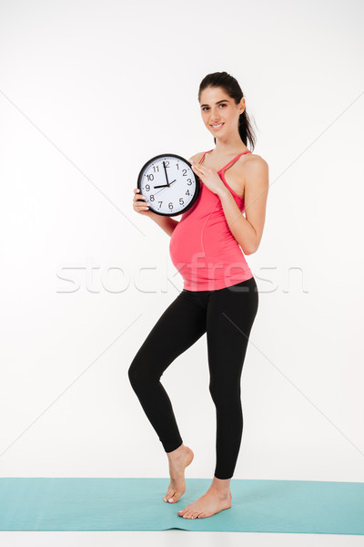 Portrait of a smiling healthy pregnant woman holding alarm clock Stock photo © deandrobot