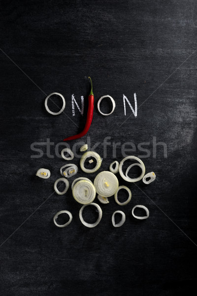 Cut onion and chilli pepper over dark chalkboard background Stock photo © deandrobot