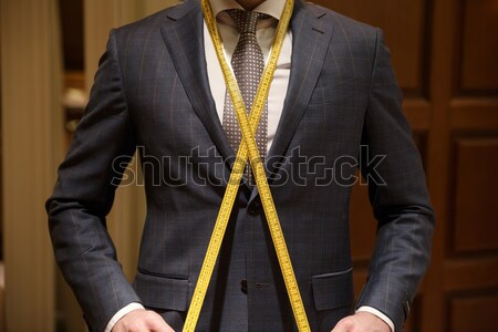 Cropped image of man with measuring tape on neck Stock photo © deandrobot