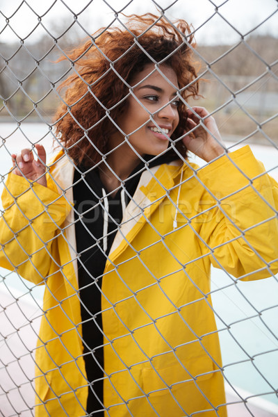 Happy african curly young lady standing near fence outdoors Stock photo © deandrobot