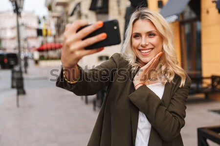 Cheerful curly young lady with shopping bags. Focus on card. Stock photo © deandrobot