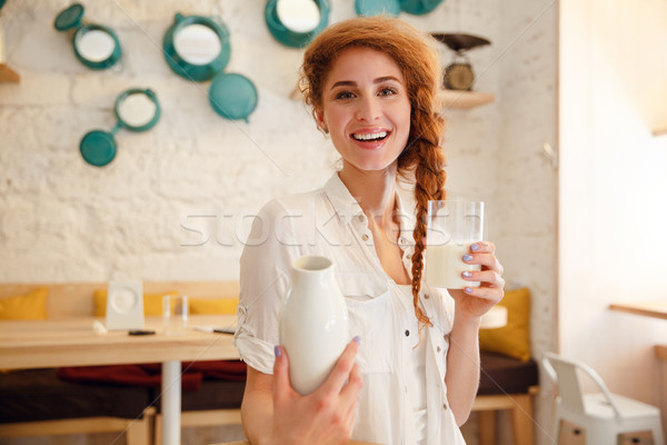 Portrait of a happy red head woman holding bottle with milk Stock photo © deandrobot