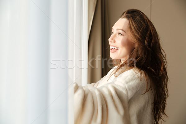 женщину халат улыбаясь глядя окна Сток-фото © deandrobot
