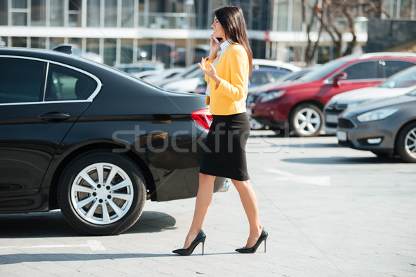 Young busy business woman walking across the street Stock photo © deandrobot