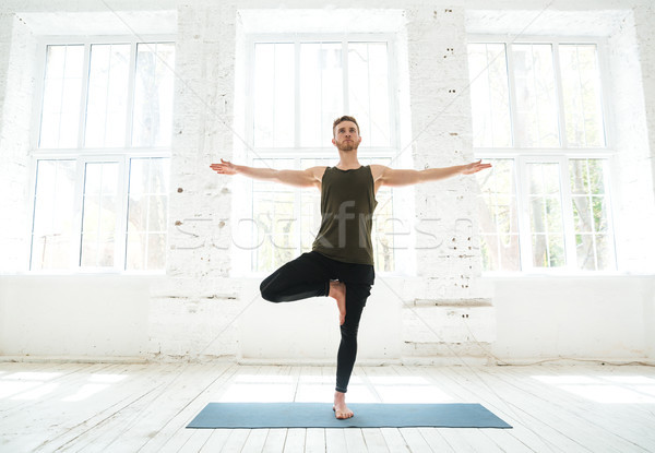 Concentrated young man parctising yoga pose on a fitness mat Stock photo © deandrobot