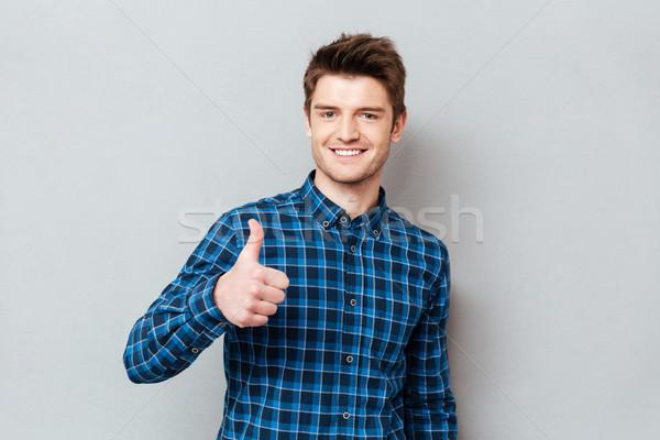 Młodych radosny student człowiek kciuk Zdjęcia stock © deandrobot