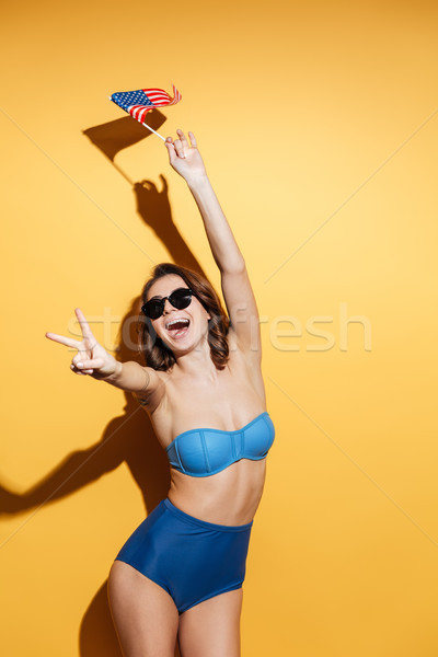 Happy woman in swimwear holding USA flag showing peace gesture. Stock photo © deandrobot