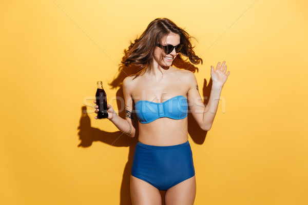 Smiling young woman in swimwear holding aerated water. Stock photo © deandrobot