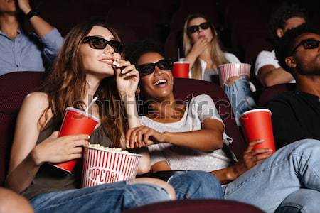 Happy friends sitting in cinema watch film eating popcorn Stock photo © deandrobot