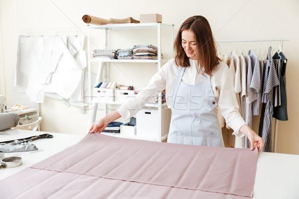 Woman seamstress spreading fabrics in workshop Stock photo © deandrobot