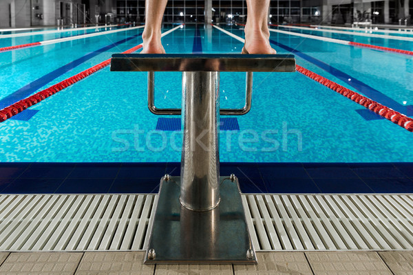 Man's feet standing on the starting blocks Stock photo © deandrobot