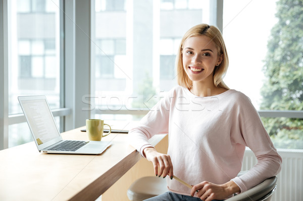 Cheerful lady sitting in office coworking while using laptop Stock photo © deandrobot