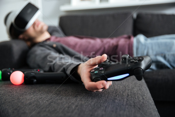 Man lies on sofa wearing 3d glasses holding joystick. Stock photo © deandrobot