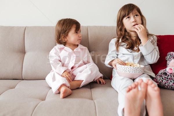 Irmã olhando mais velho alimentação pipoca sala de estar Foto stock © deandrobot