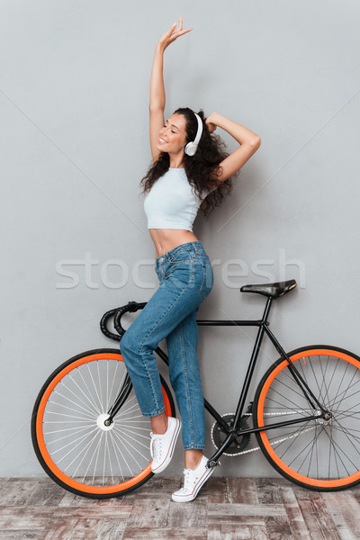Full length image of pleased curly woman standing with bicycle Stock photo © deandrobot