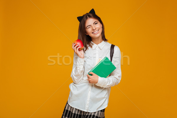 Portrait of a pretty schoolgirl holding books with apple Stock photo © deandrobot