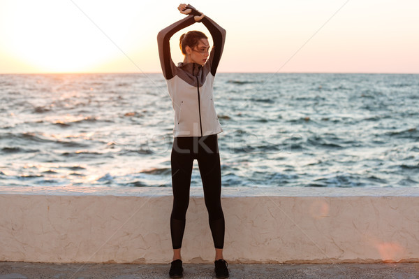 Full-length photo of young pretty woman in sport wear doing stre Stock photo © deandrobot