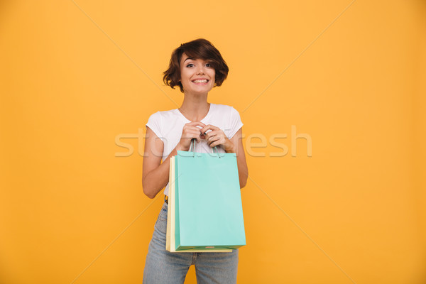 Portrait of a smiling satisfied girl holding shopping bags Stock photo © deandrobot